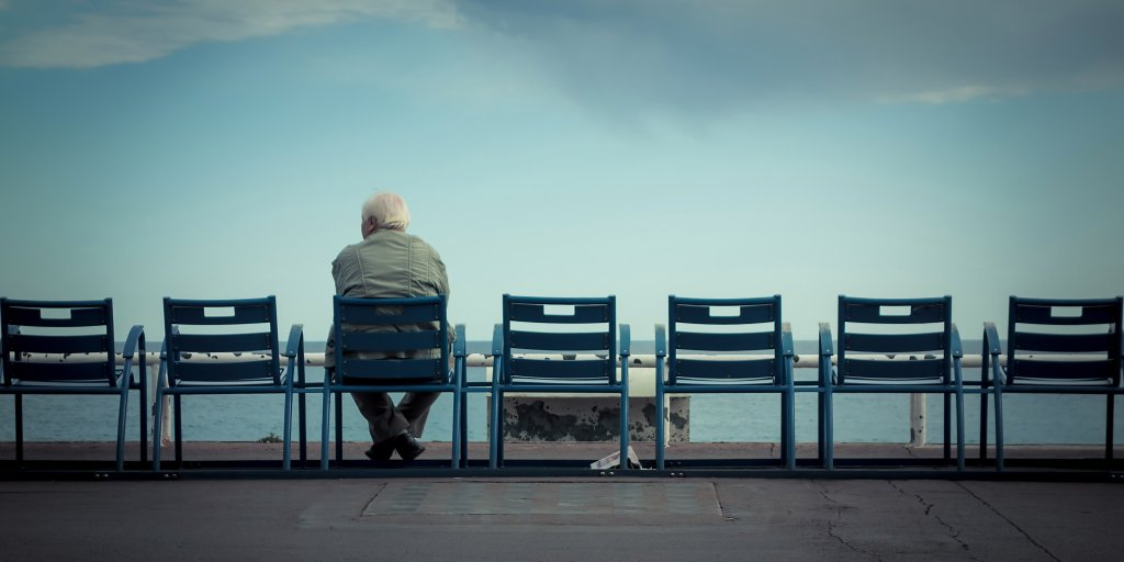 Rear View Of Man Sitting On Chair Against Cloudy Sky